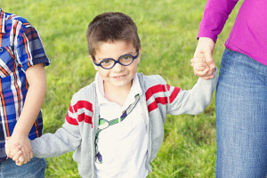 Young child with glasses holding hands