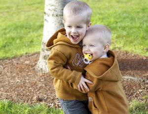 Two siblings dressed alike hugging
