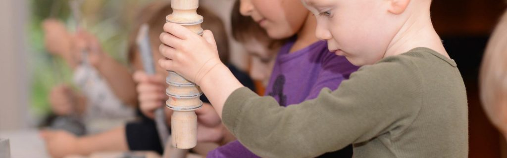 Child plays with wooden dowel