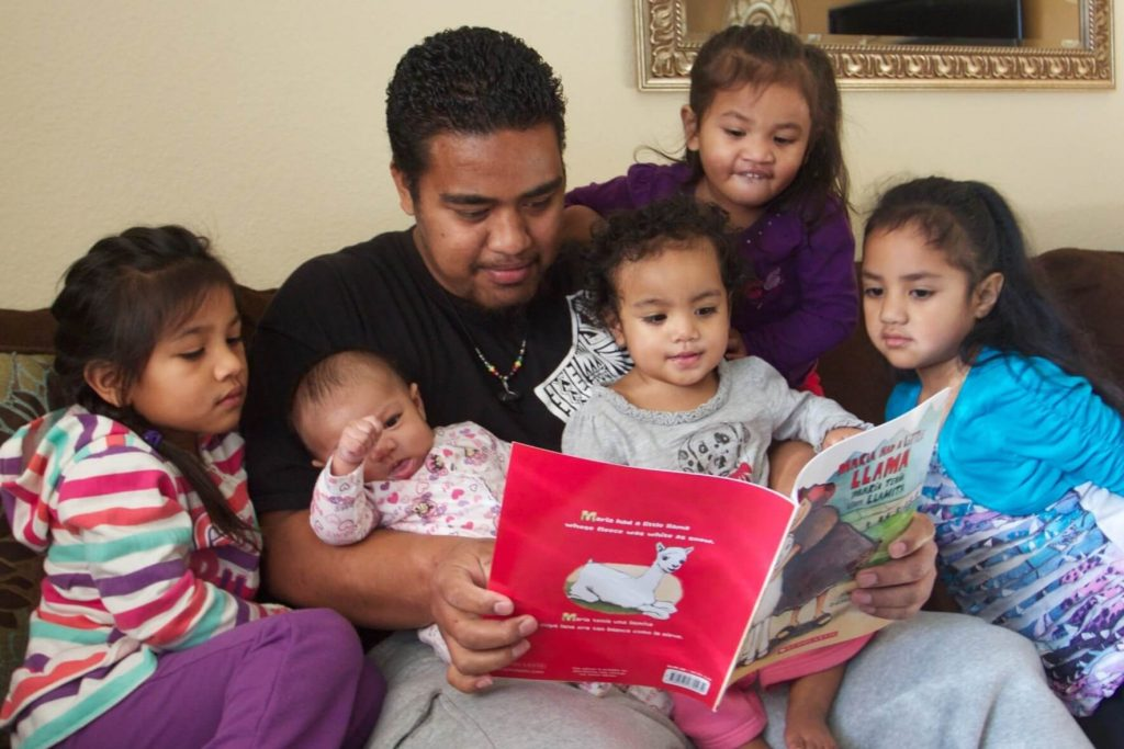 Parent reads to five children of different ages
