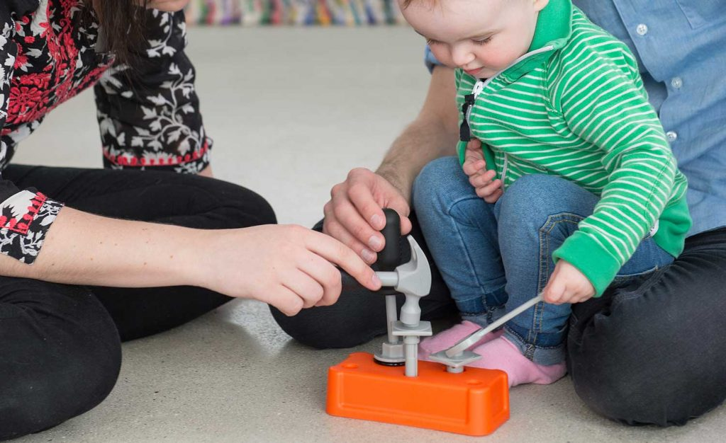 Small child plays with plastic tools as parents watch