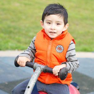 Child in orange vest plays in playground