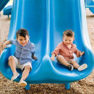 Two happy chidden on blue slide