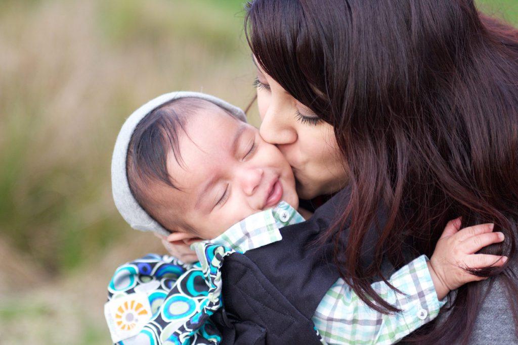 Parent kisses baby on cheek