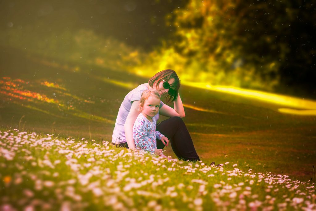 Parent with child sitting on grassy hill outside