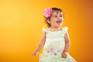 vroom portrait of toddler laughing in summer dress with pink flower