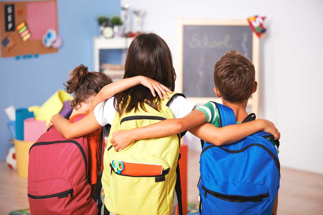 Children arm in arm with backpacks facing away from the camera at school