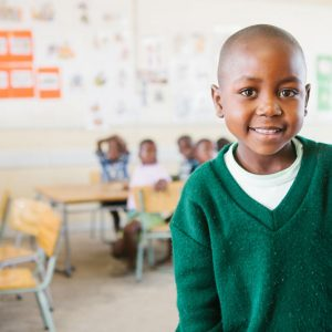 Young boy in green sweater in classroom