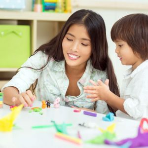 Teacher plays crafts with toddler in classroom
