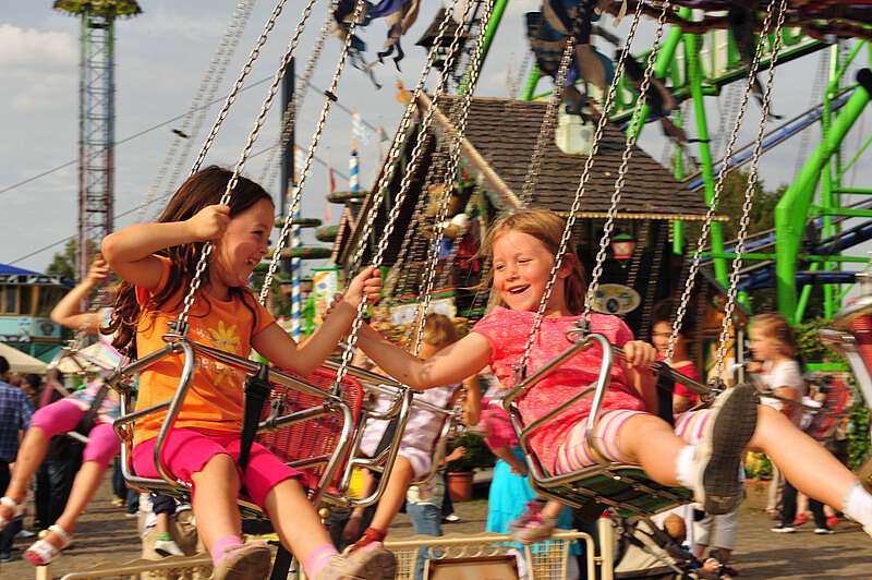 Children on a carnival ride swing