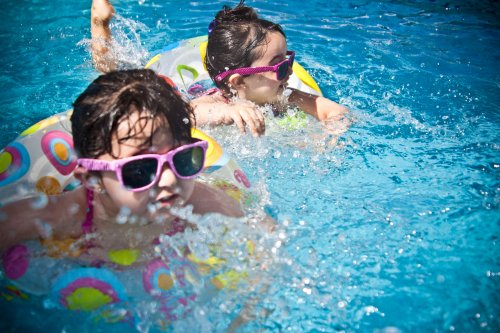 Children in pool with sunglasses splashing