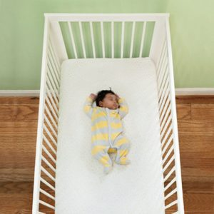 Infant sleeping in crib in pajamas