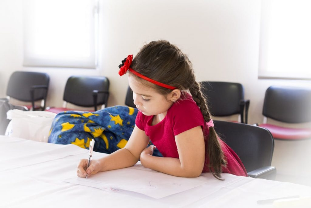 Young child writes on paper with pen
