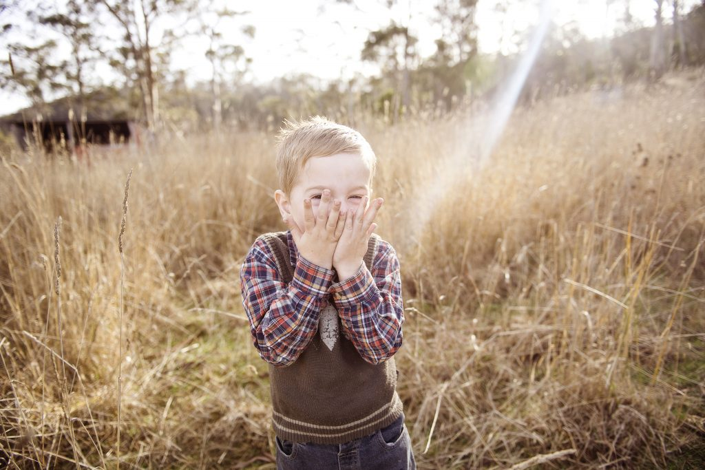 Young child plays in dry grass