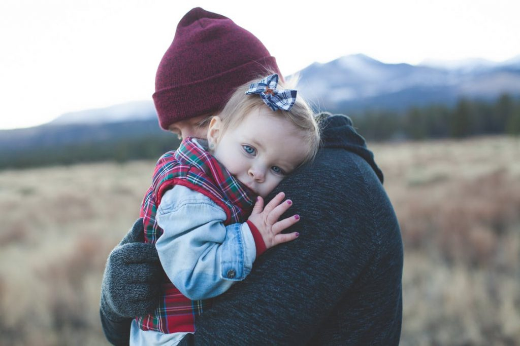 Parent holding and embracing young child in winter setting