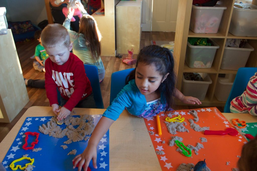 Children play with play sand in classroom