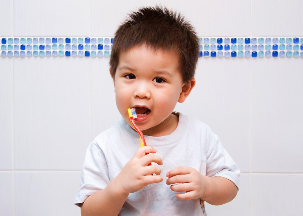 Child brushes teeth in bathroom