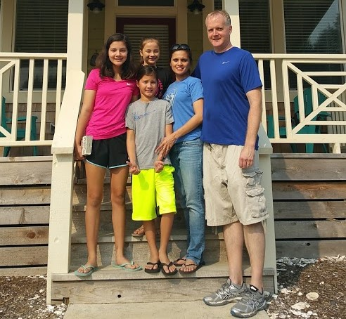 Flier: Family stand on front steps of house