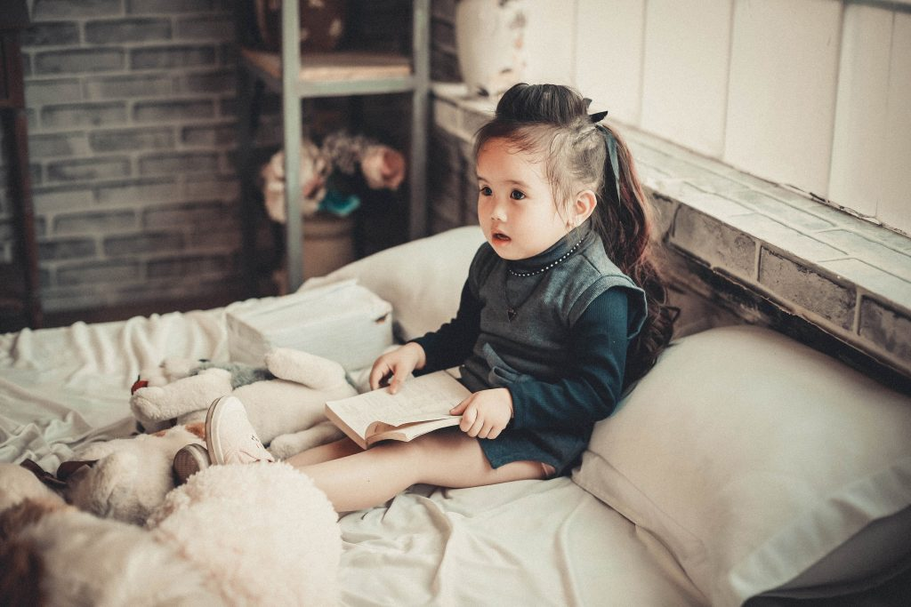 Child sits on bed reading a book