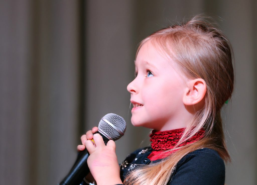 Child sings into microphone
