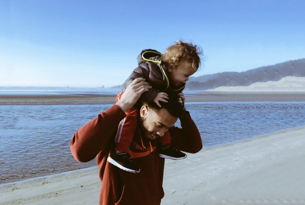 Parent holds child on shoulders on beach