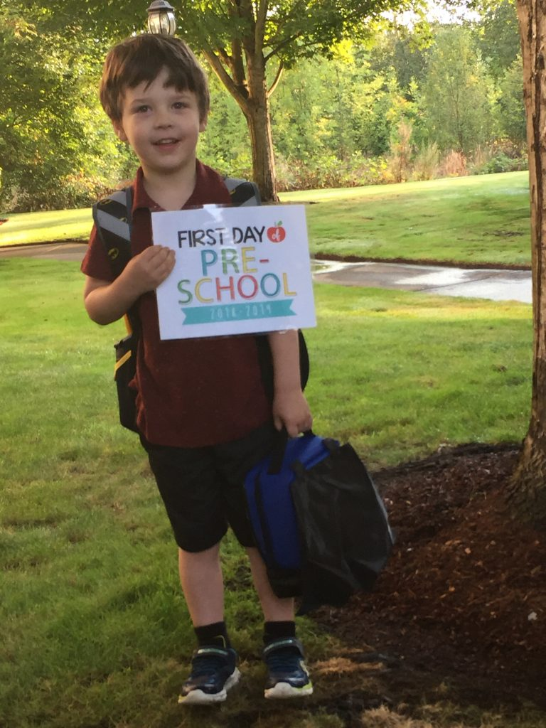 """Child holding sign """"First day of Pre-School"""""""