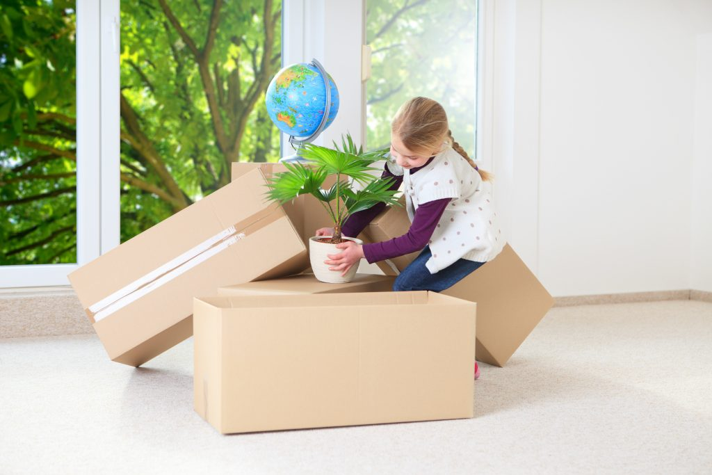 Small girl packs boxes and a plant