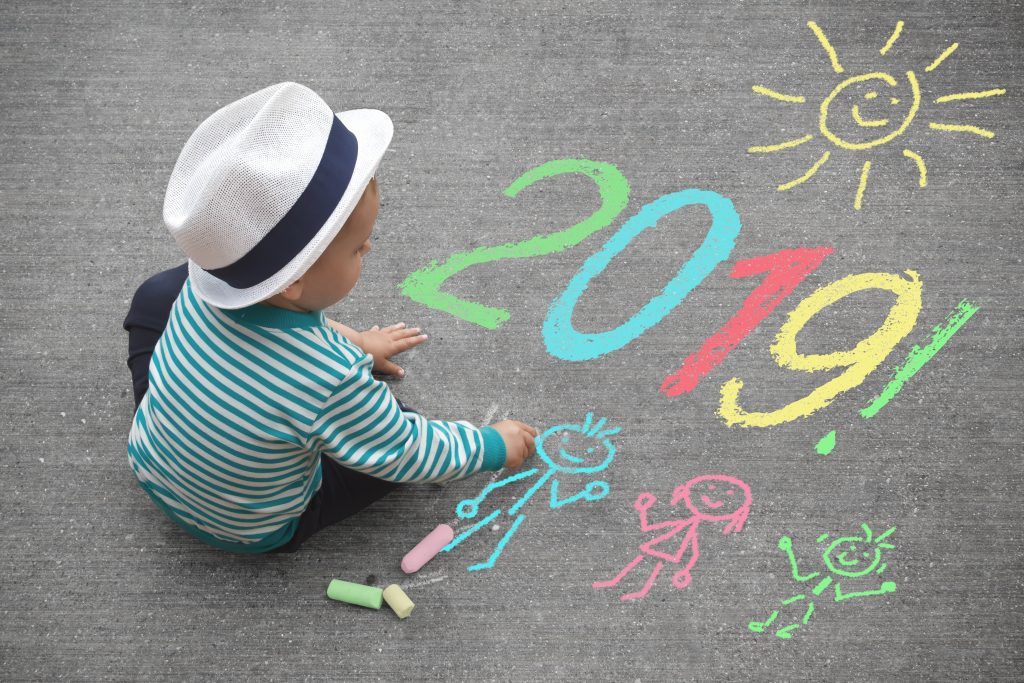 Small child writes 2019 in chalk on pavement