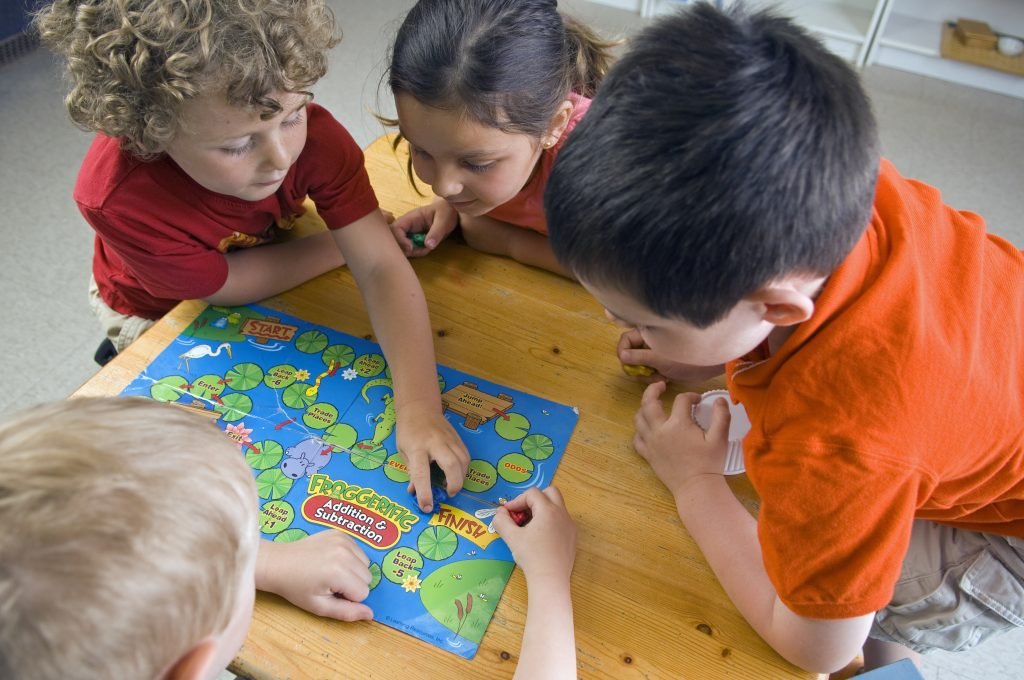 Small children playing a math game in a classroom