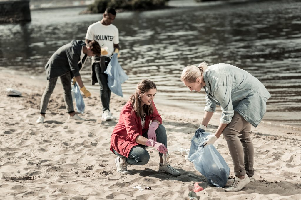 Group of Volunteers picking up trash off the beach