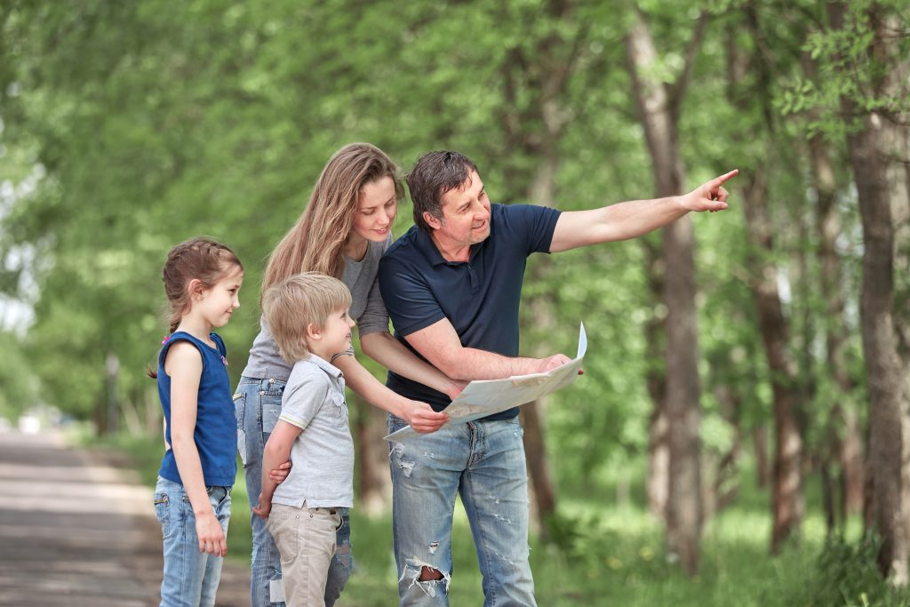 Family looking at map outside and point