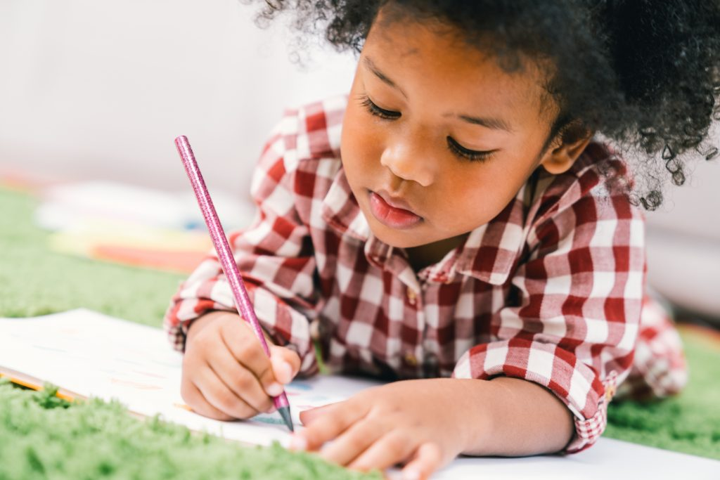 Small child writing on paper on the carpet