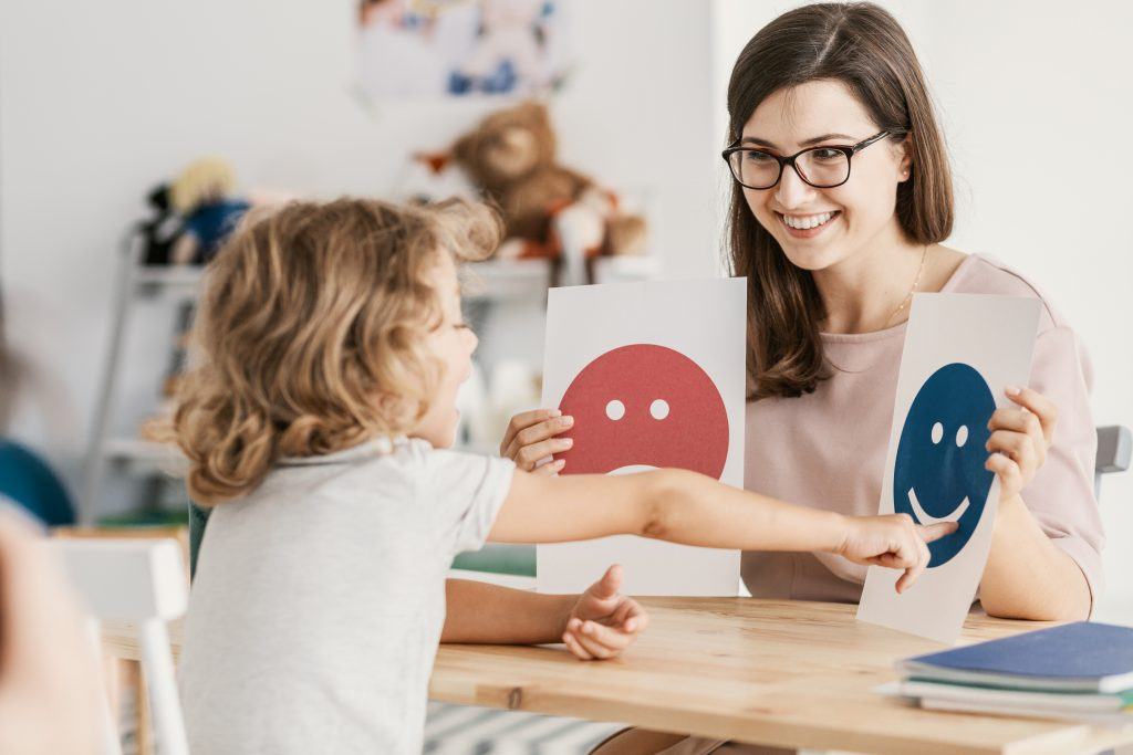 Child points at teacher holding images of happy and sad faces