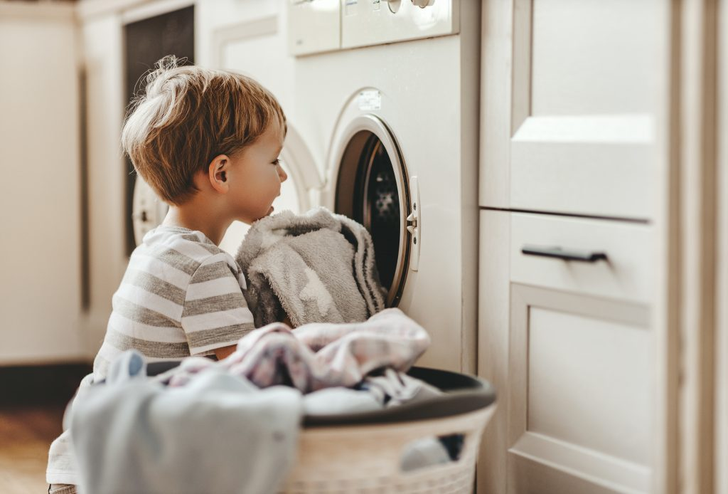 Child loading laundry in dryer from basket