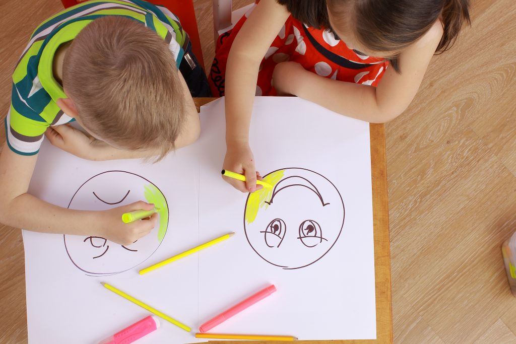 Two children coloring happy and sad faces