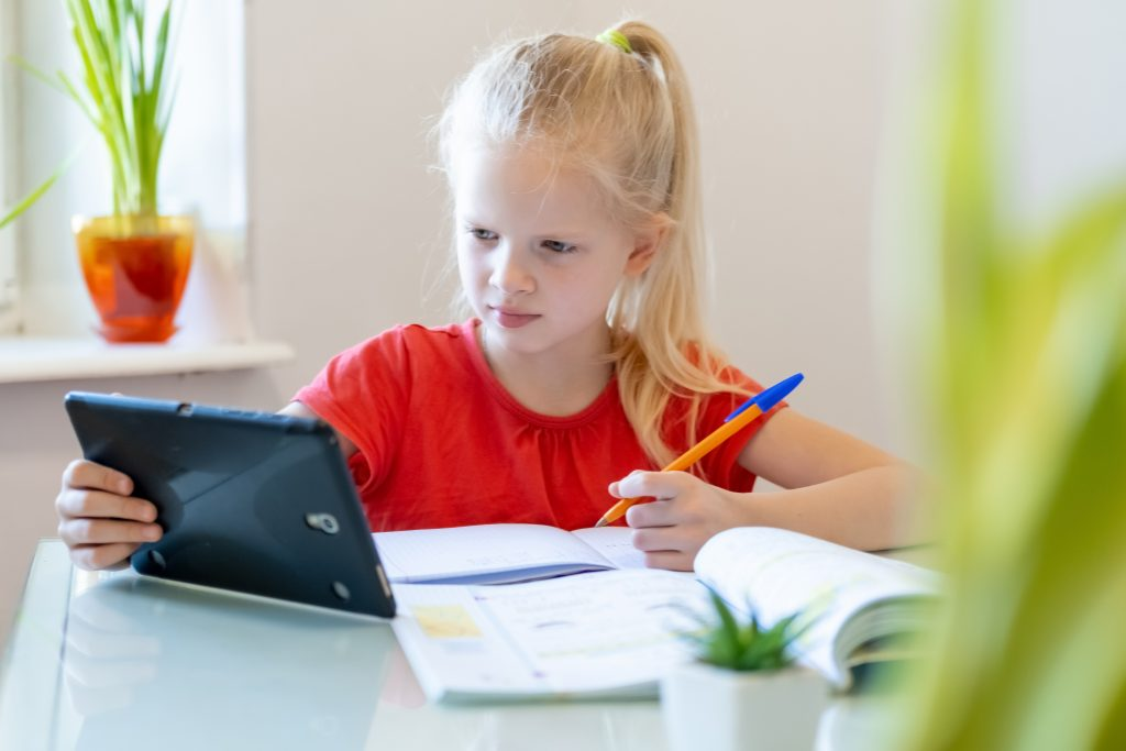 Young girl with a pen and paper and a tablet computer