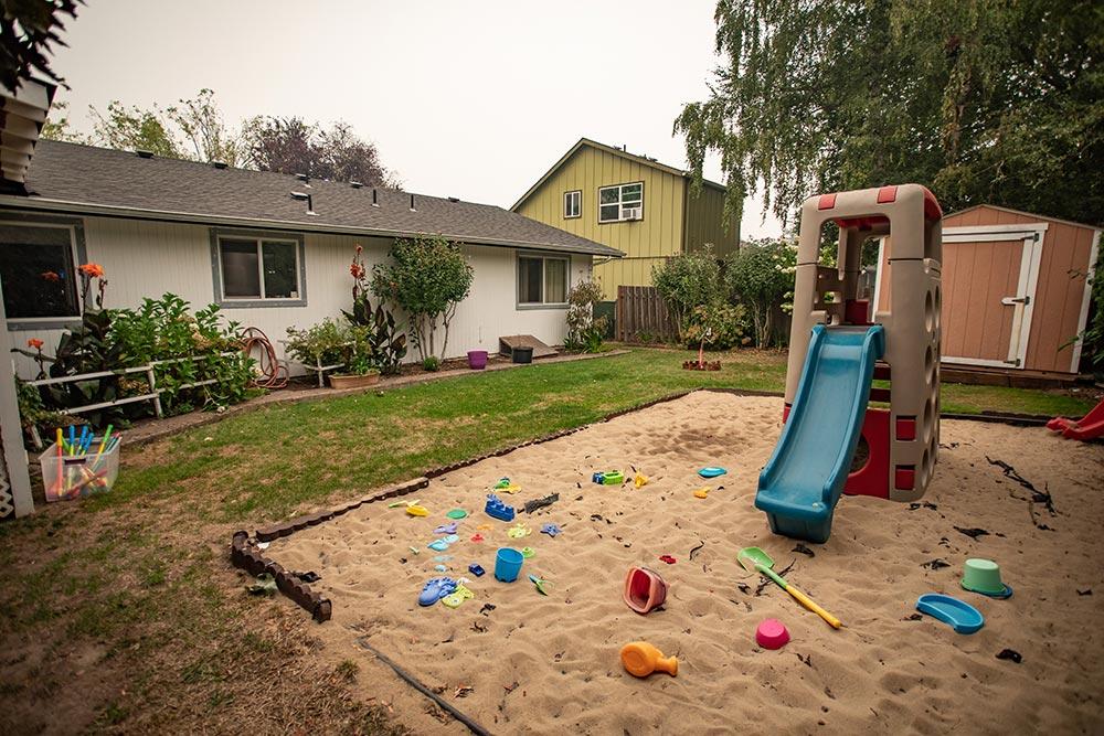 Abuela's Daycare Aprendiendo y Jugando playground with sandbox and toys