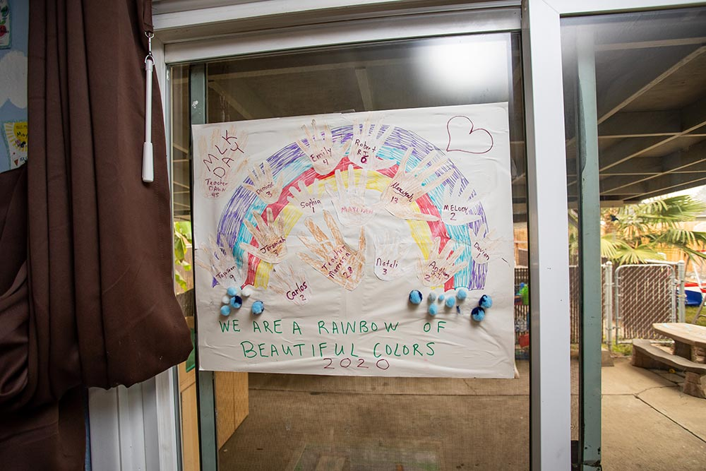 Busy Beez Daycare sign on door of Rainbow and children's hands that says,