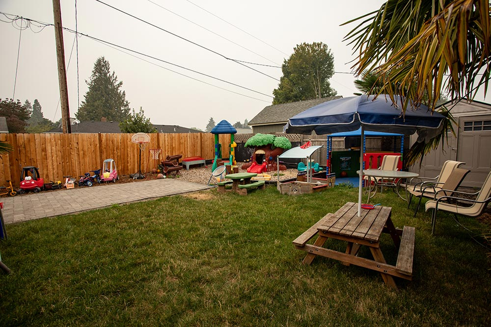 Busy Beez Daycare yard with picnic table, paver patio and toys