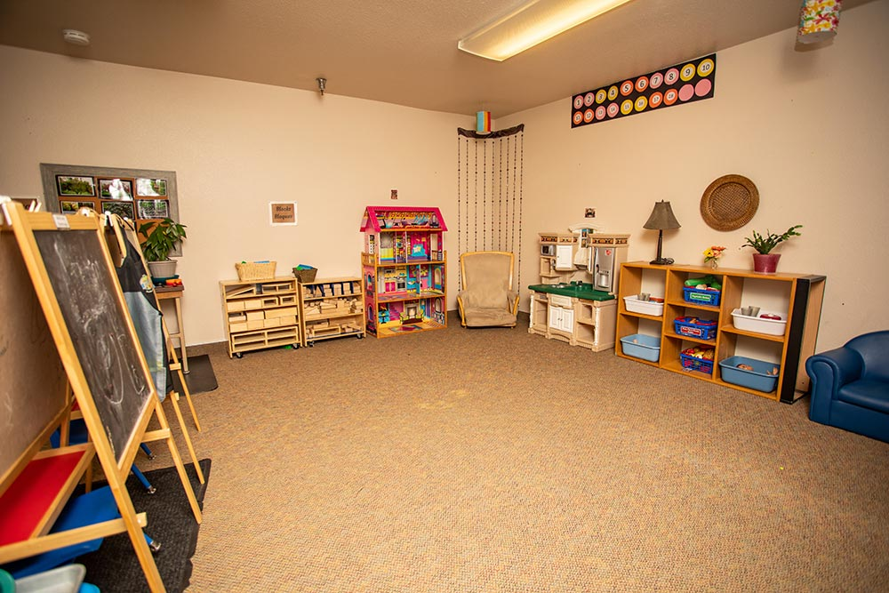 Faces of America play area with chalkboard, blocks, playhouse and chairs
