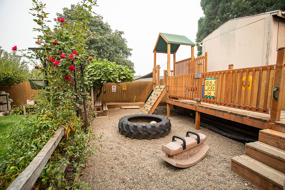 Island Adventures Childcare and Preschool playground with tire and climbing wall