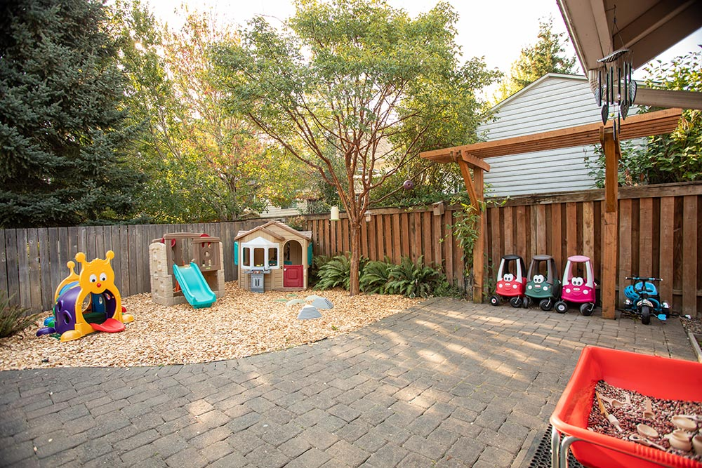 Little Smiles Preschool outdoor play area with kid cars and playhouse